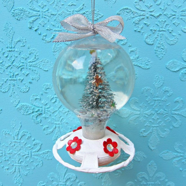 Make a snow globe from a hummingbird feeder. Use Dollar Tree items to create a cute piece of holiday decor this winter season!