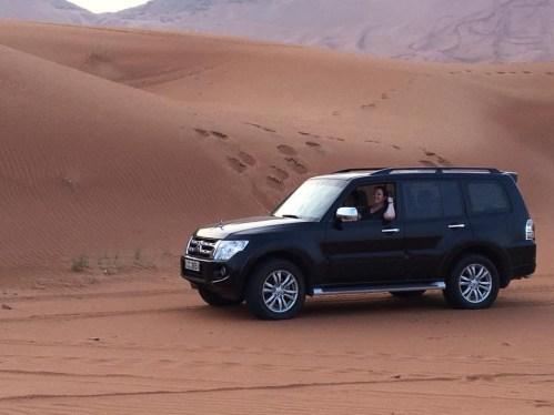 Black Mitsubishi Pajero with desert dunes in background
