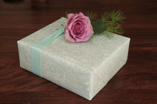 Gift wrapped in pale blue paper and trimmed with a pale blue ribbon and pink rose flower