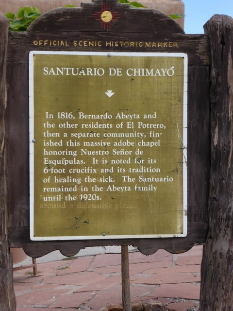 El Santuario de Chimayo is a National Historic Landmark. The marker notes the healing properties of the holy dirt.