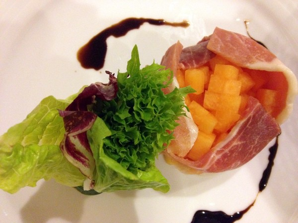 Room service presentation of prosciutto and melon