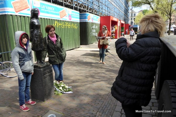 A mother poses with her daughter beside a statue of Anne Frank