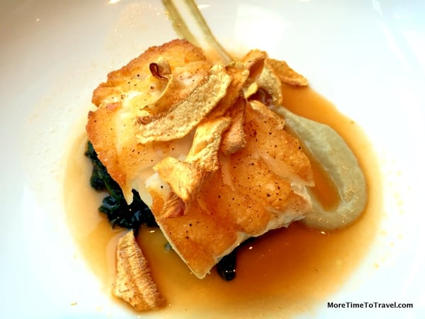 Seared black cod on a bed of baby spinach with artichokes and lobster lemongrass broth