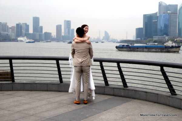 Bride and groom stop for wedding pictures on the waterfront promenade near The Bund in Shanghai