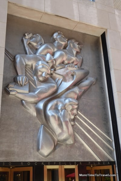 """News, a bycast stainless steel Art Deco plaque, depicts five journalists """"getting a scoop""""- at the former Associated Press Building"""