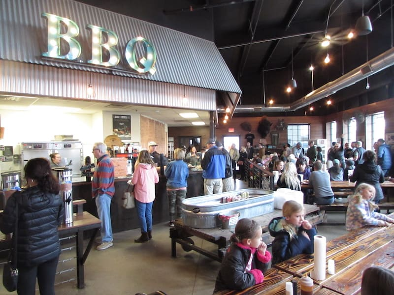 Busy BBQ joint with free beer in the middle
