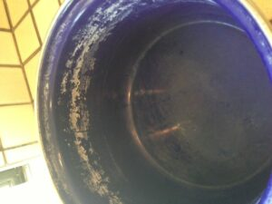 My blue pot full of mineral deposits before soaking it in vinegar.