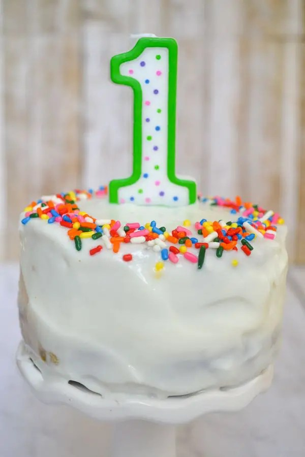 a white frosting covered healthier smash cake topped with a 1 candle with rainbow sprinkles