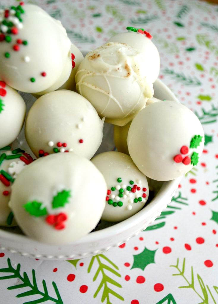 a stack of white eggnog latte truffles with holiday sprinkles in a white bowl on christmas wrapping paper