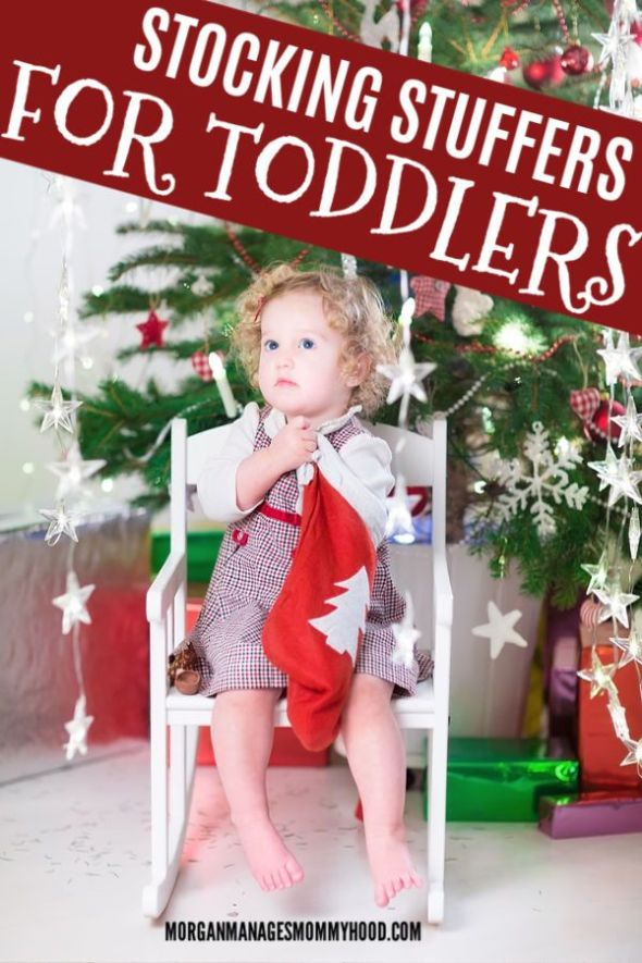 a toddler in a white chair in front of a christmas tree looking through a red stocking for toddler stocking stuffers