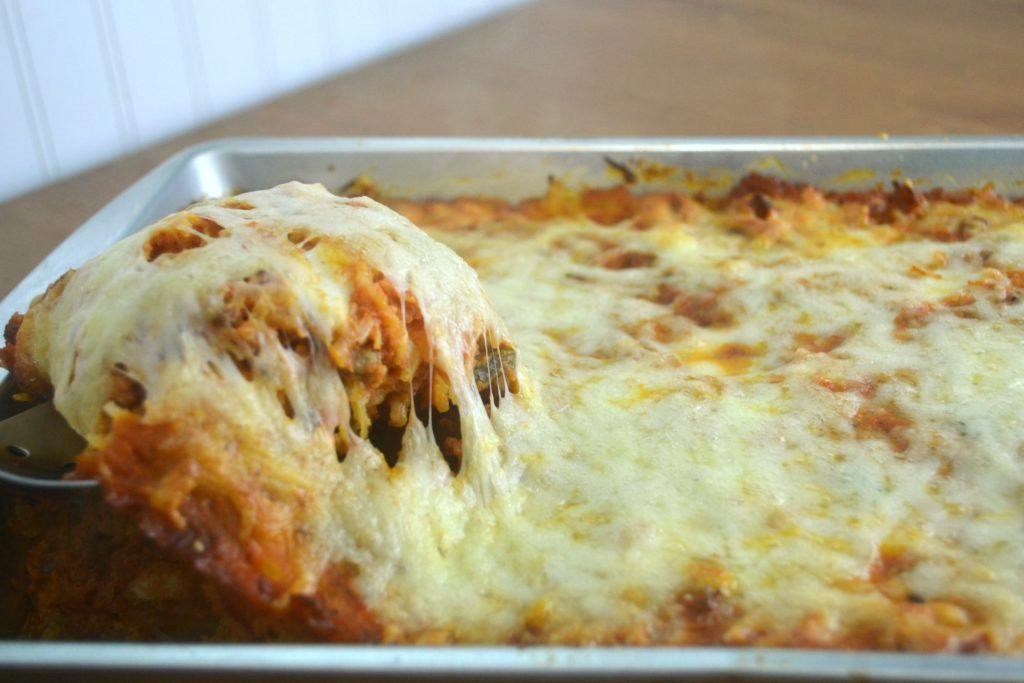 a large silver serving spoon scooping out low carb pizza casserole from a silver baking pan covered in stretching cheese.