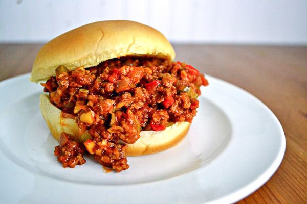 healthier sloppy joe mix falling out of a soft potato roll on a white plate