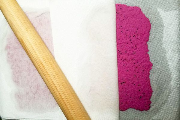 a rolling pin layered with pink seed paper and paper towels to dry