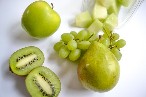 green fruits like a pear, grapes, a green apple, honeydew melon and a sliced kiwi on a white background