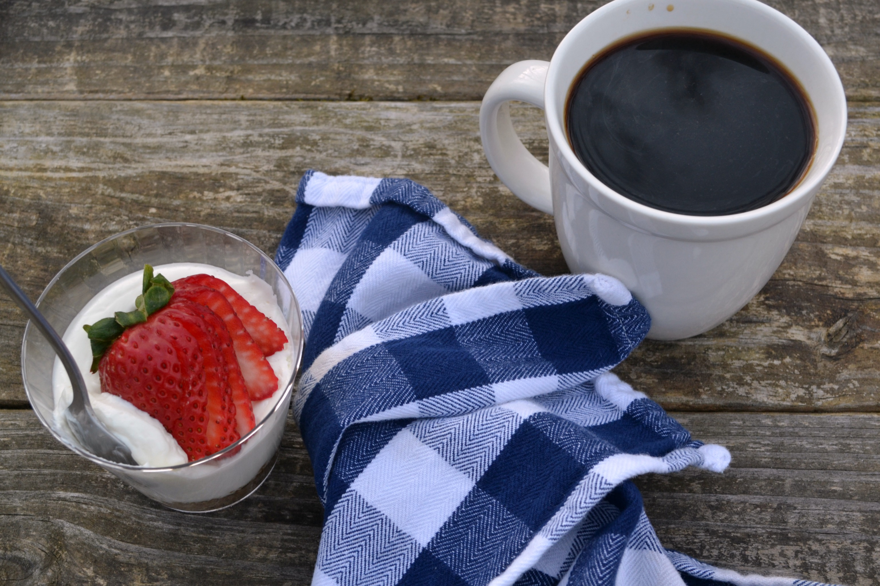 a photo of a breakfast cheese cake with a sliced strawberry on top with a cup of coffee next to it