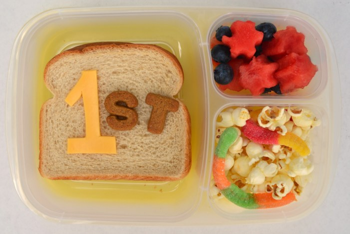 a first day of school lunch with popcorn and watermelon cut like flowers with a sandwich with 1st on the top