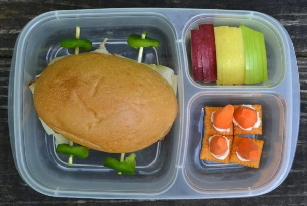 a hoagie roll turned into a race car with skewers and pepper rounds with traffic light apples and traffic cone carrots.