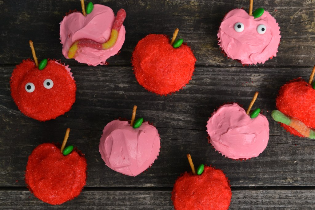 healthy apple muffins in pink and red made to look like apples on a worn wooden table
