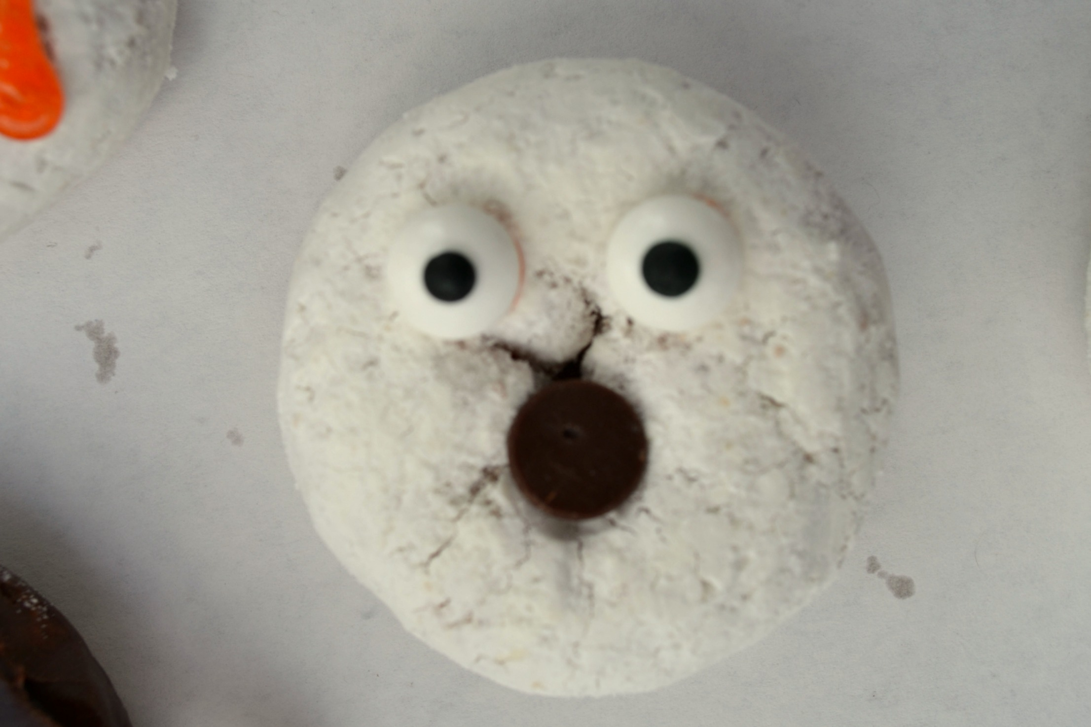 a powdered sugar donut made to look like a ghost with 2 candy eyes and a chocolate chip