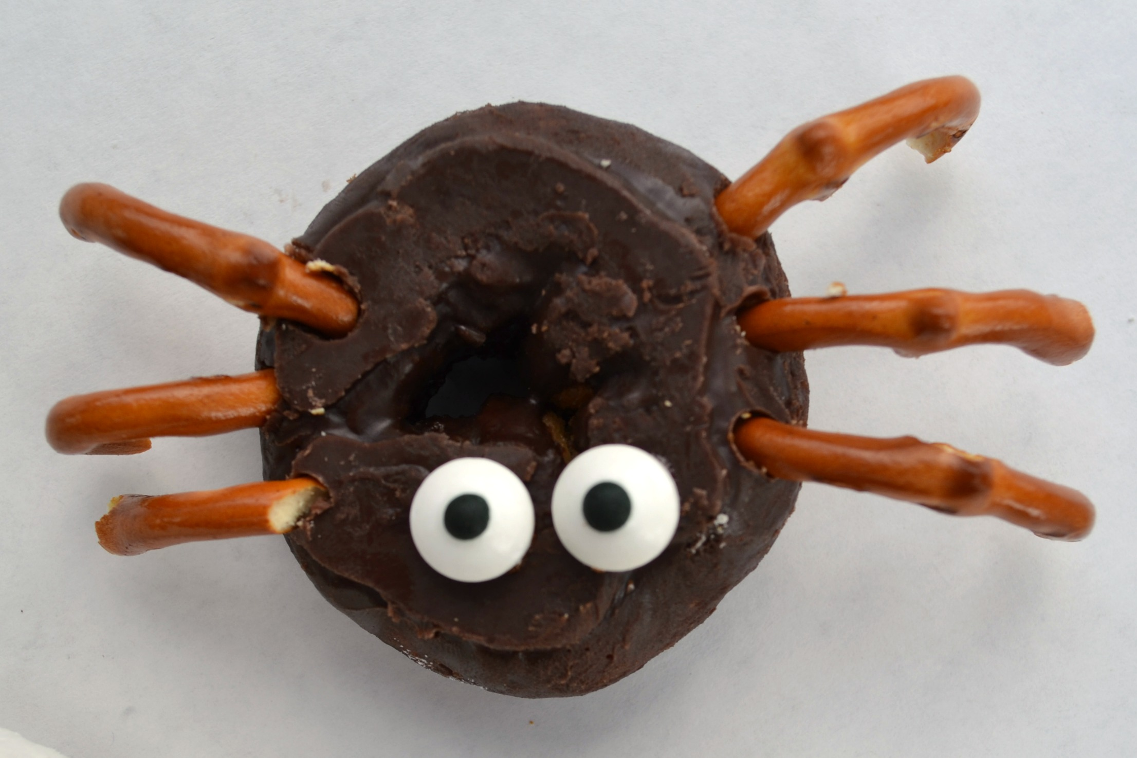 a spider donut using pretzels and candy eyes in a chocolate frosted mini donut