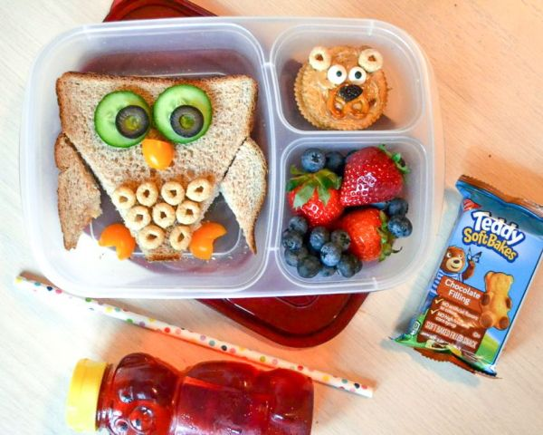 an owl lunch box with a honey bear drink, fresh fruit, and a sandwich that looks like an owl