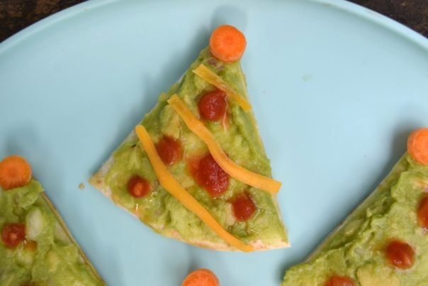 a Christmas snack for kids - a christmas tree quesadilla on a blue plate topped with green guacamole, red salsa 'ornaments', shredded cheese as garland, and an orange carrot on top.