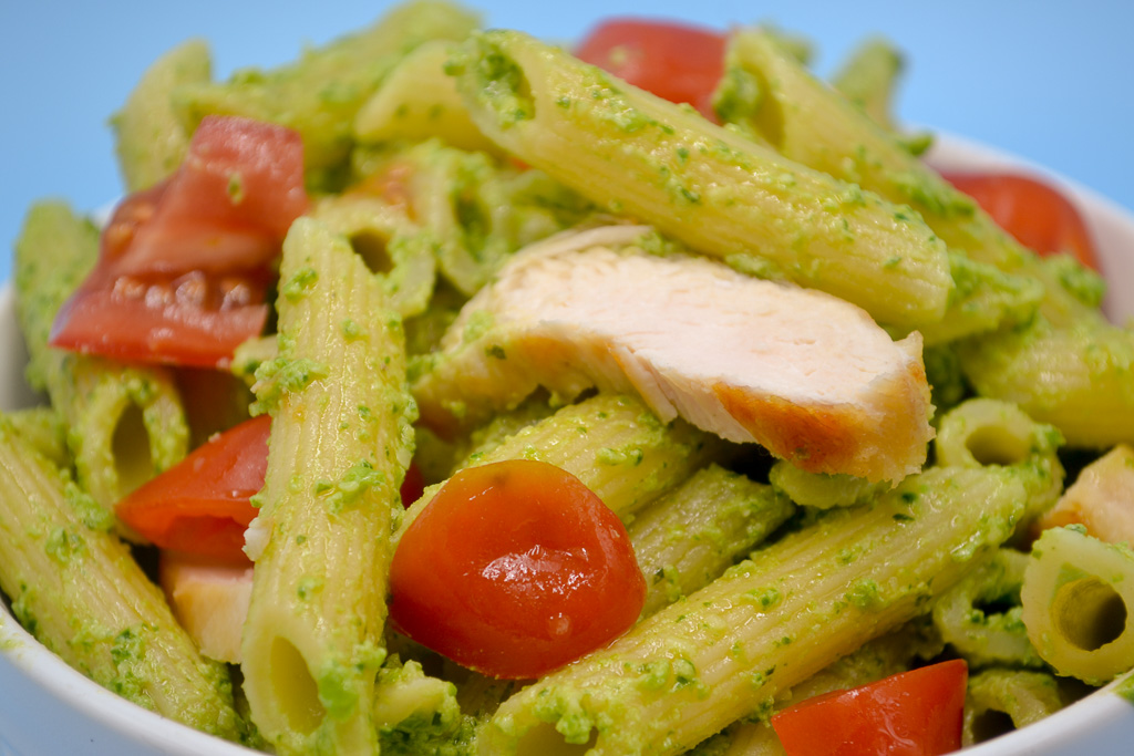 a close up of Veggie Pesto Pasta Sauce. Penne noodles covered in sauce with grilled chicken and red grape tomatoes.
