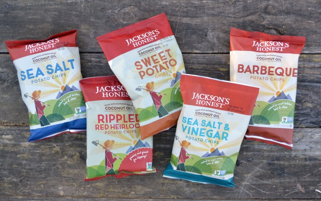 a variety of jackson's honest snack backs on a weathered old wooden picnic table