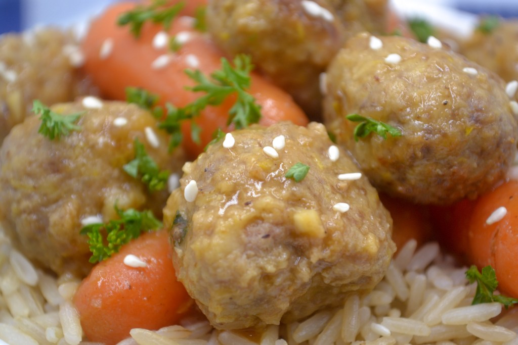 a closeup hidden veggie asian meatballs and baby carrots over brown rice