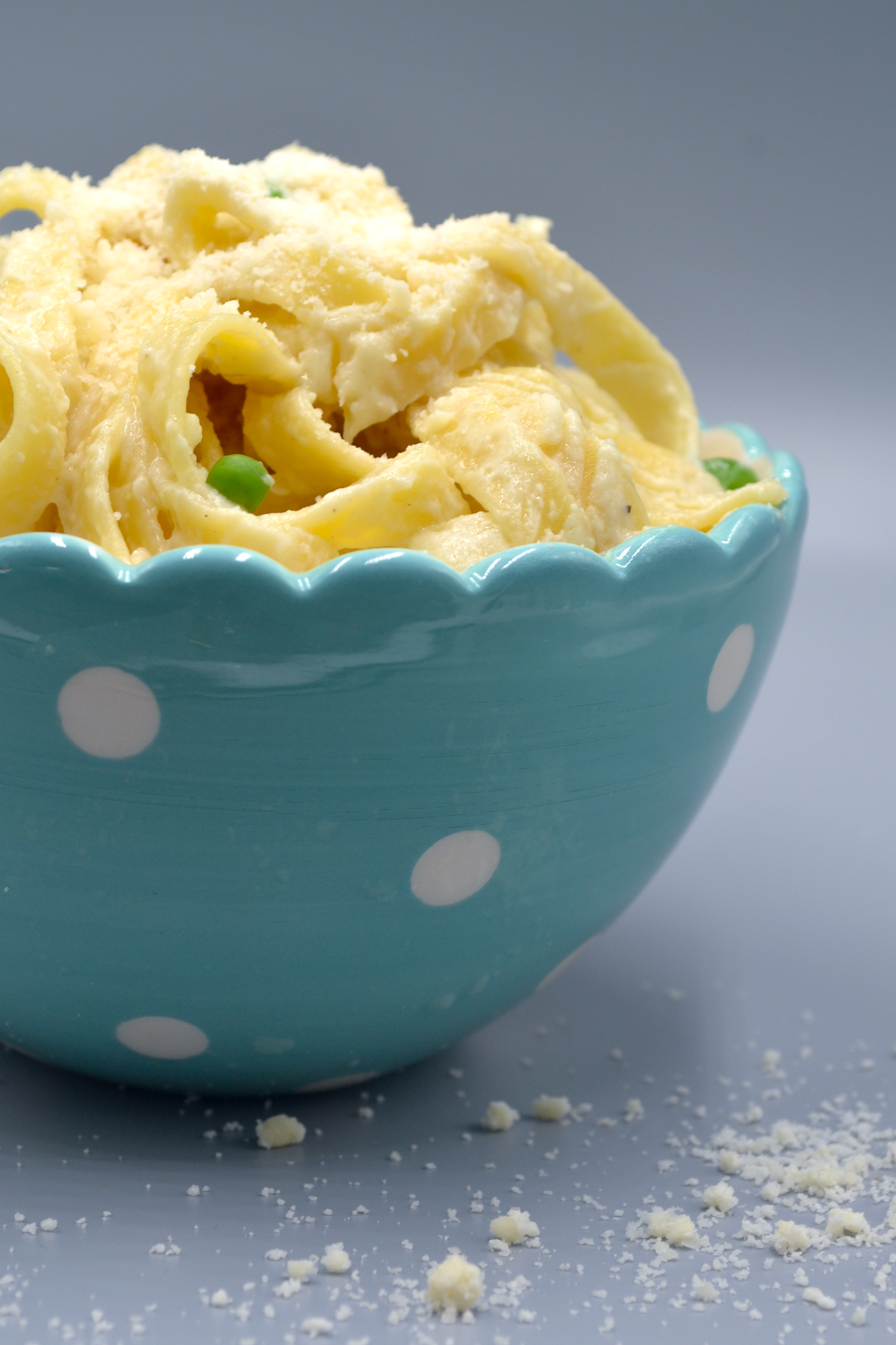 a bowl of fettuccine and peas covered in veggie alfredo and topped with parmesan cheese in a blue bowl with white polka dots on a grey background with parmesan cheese on the base.