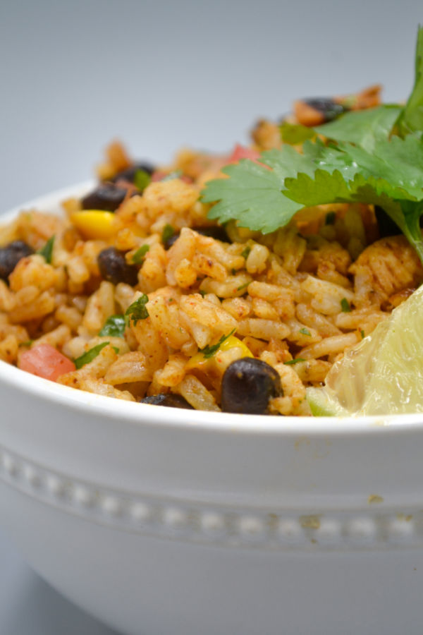 a white bowl filled with Mexican fried rice, fresh cilantro, and a wedge of lime.