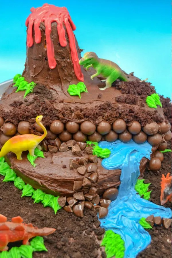 a dinosaur diaromma on a dinosaur birthdya cake with chocolate cake and frotsing, a cake volcano and a frosting waterfall