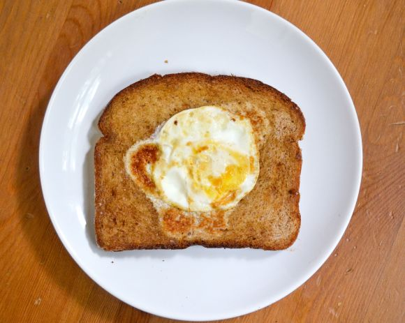 a basic egg in a hole recipe using a circle cutter on a white plate
