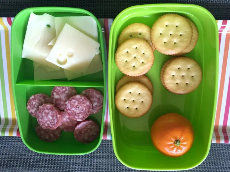 A photo of a DIY lunchable with salami, swiss, crackers, and a clementine in a green sectioned container