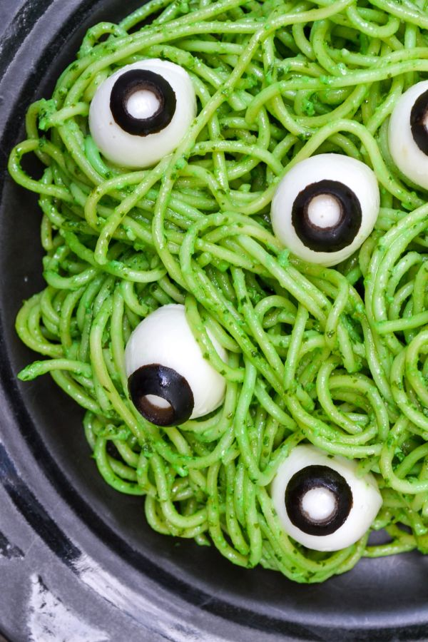 spooky eyeball halloween pasta is pictured on a black plate - bright green spaghetti noodles covered in veggie pesto and topped with mozzarella eyeballs
