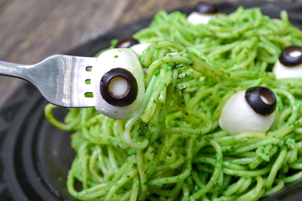a silver fork holding a mozzarella eyeball on a black plate filled with green halloween spaghetti