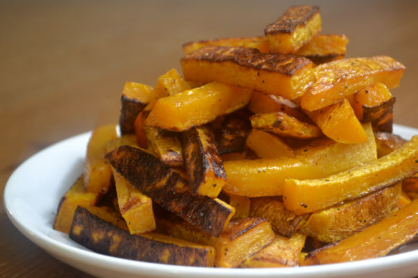 a plate filled with stacked butternut squash fries with a wood background