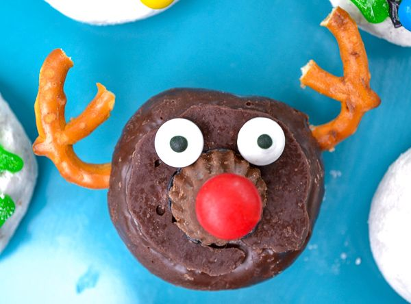 a chocolate donut with 2 pretzel antlers and candy to make it look like rudolph the red nose reindeer on a blue plate.