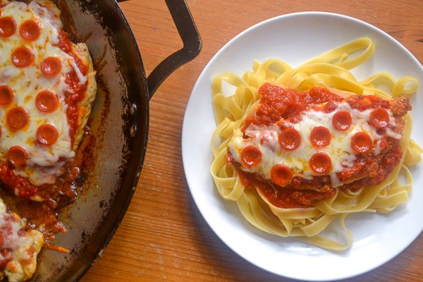 a white plate with pepperoni chicken pizza on top of fettuccini, with a pan to the left baking pizza chicken