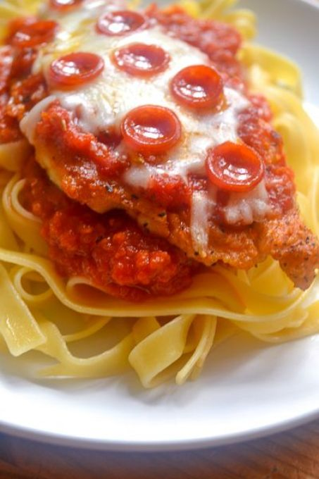 a white plate with fettuccine topped with sauce and a piece of pizza chicken topped with cheese and mini pepperoni