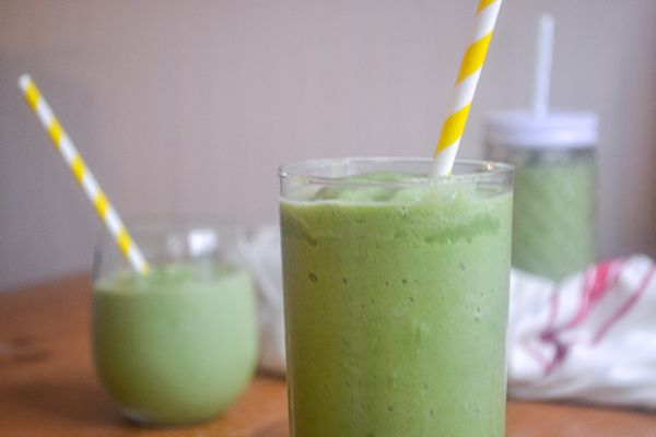 Three spinach smoothies with straws in different shaped glasses on a wood table with a white background