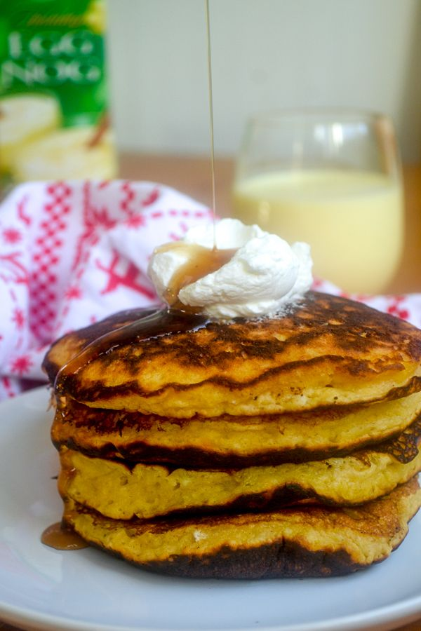 a stack of eggnog pancakes with a dollop of whipped cream with maple syrup being poured on top