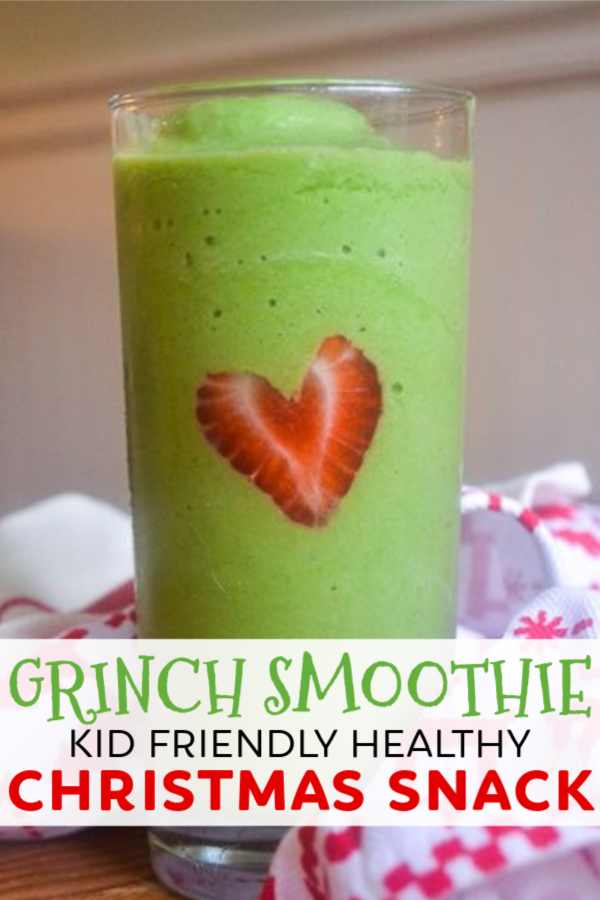 A green smoothie in a tall glass with a strawberry cut into the shape of a heart to make a christmas smoothie