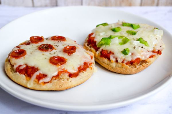 a photo with two english muffin pizzas on a white plate with pepperoni and green pepper