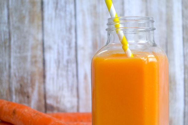 horizontal image of an orange smoothie with a yellow striped paper straw in front of a wood planked wall