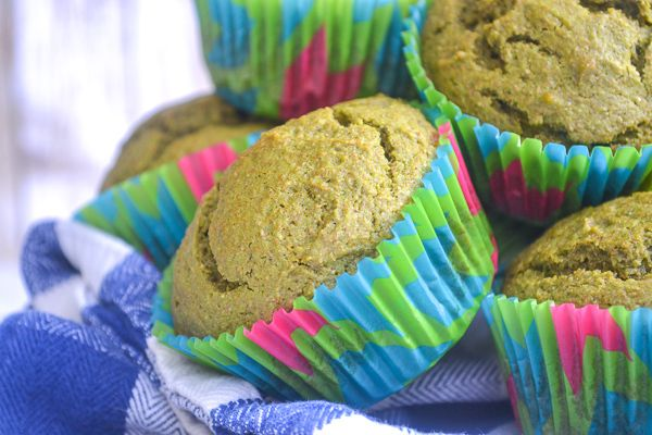a close up of a green spinach muffin with colorful muffin liners on a blue gingham dish towel