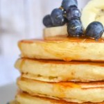 a stack of fluffy buttermilk pancakes with syrup dripping down the edges topped with blueberries and bananas