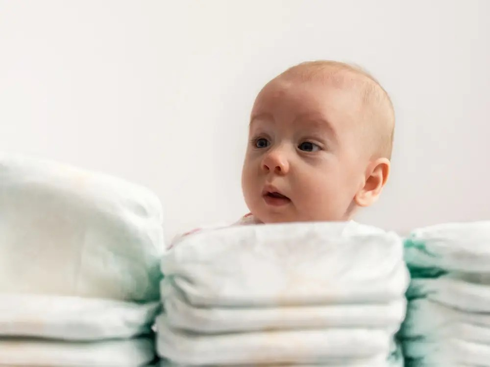 a baby looking over a large stack of diapers