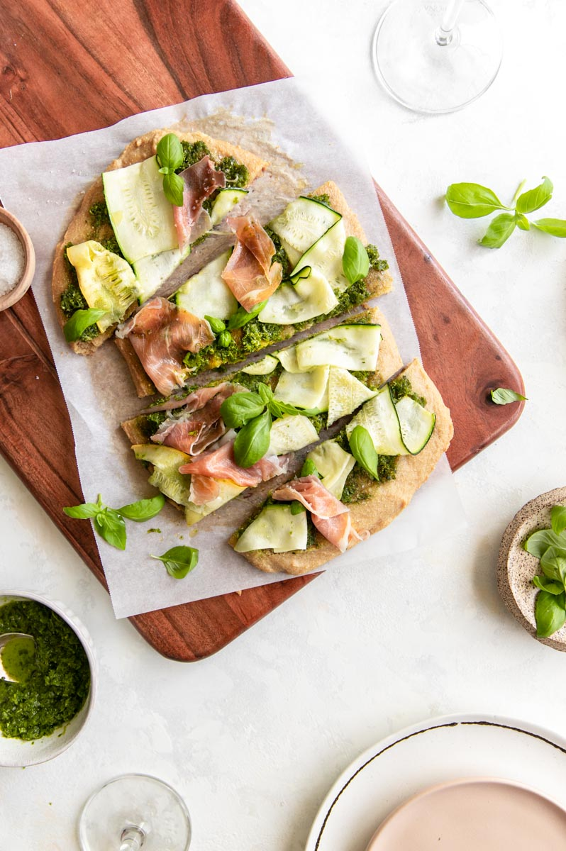 This Paleo Zucchini Pesto Flatbread Pizza is the perfect end-of-summer dinner when the summer squash are ripe and there are abundant fresh greens for the vegan pesto. Top it off with prosciutto for the perfect paleo flatbread!