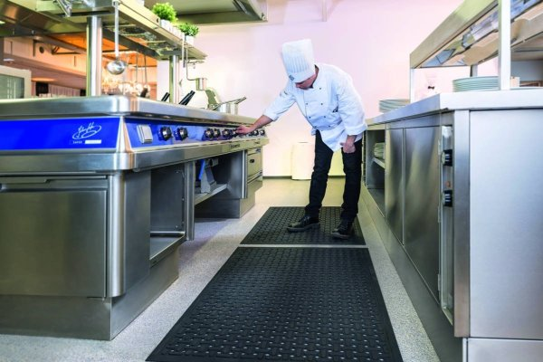 A Chief at a stove in a commercial kitchen turning a dial stood on a Morland Service Anti bacterial rubber industrial doormat